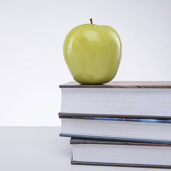 apple on a stack of text books teacher concept